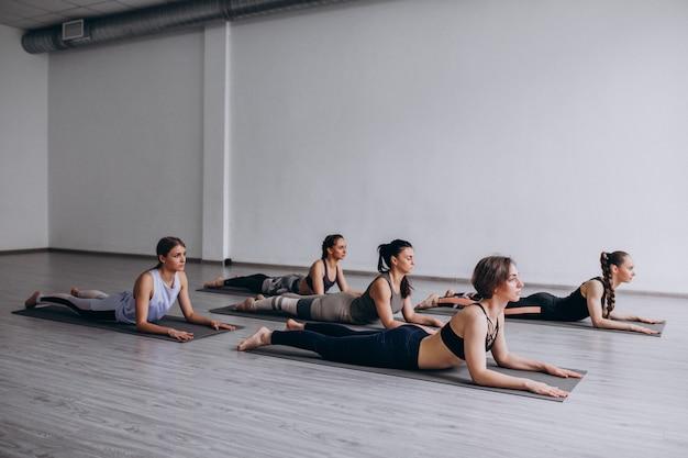Aulas em grupo de ioga dentro da academia Foto gratuita
