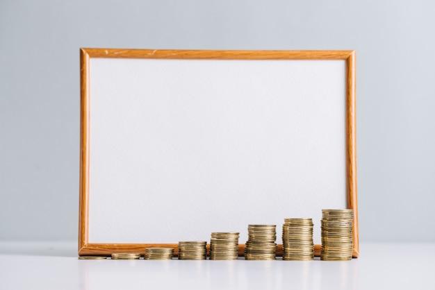 Aumentando moedas empilhadas na frente do quadro branco em branco Foto gratuita