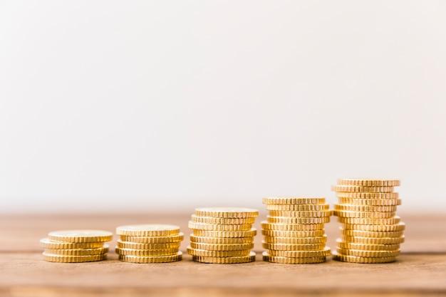 Aumentando moedas empilhadas na mesa de madeira Foto Premium