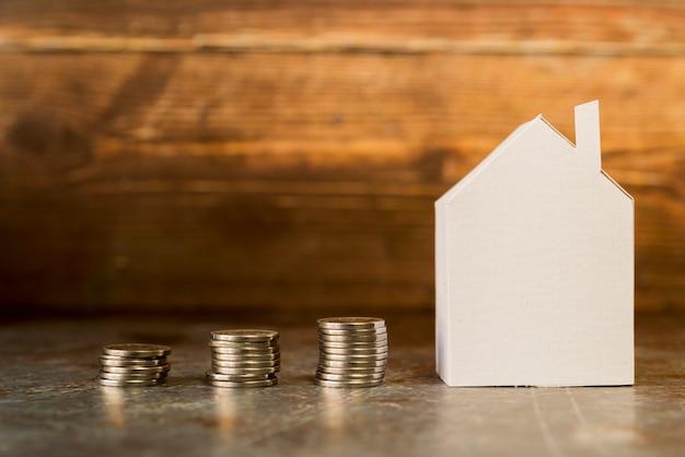 Aumentar a pilha de moedas perto da casa de papel na superfície Foto gratuita