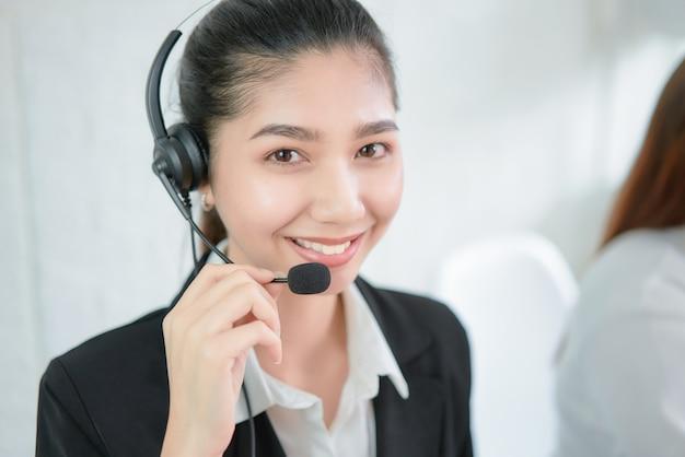 Auriculares vestindo de sorriso do microfone do consultante asiático de sorriso da mulher de negócios do operador do telefone do apoio ao cliente no local de trabalho. Foto Premium