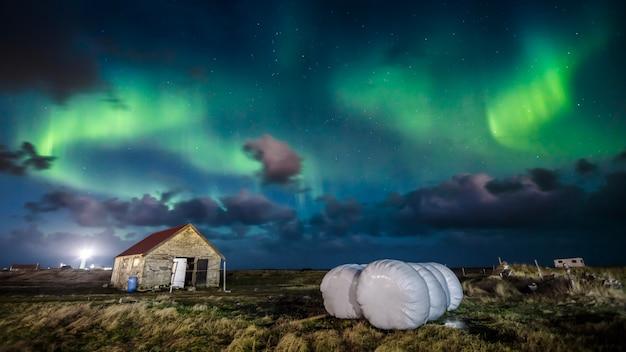 Aurora boreal (aurora boreal) sobre casa de fazenda Foto Premium