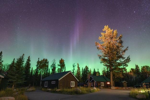 Aurora boreal, aurora boreal sobre chalé de madeira no parque nacional de jasper Foto Premium