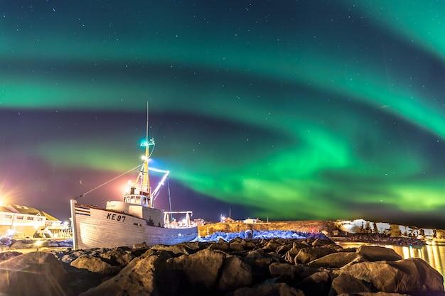 Aurora boreal colorida com um barco em primeiro plano na islândia Foto Premium
