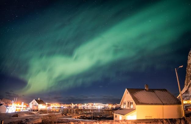 Aurora boreal dançando sobre vila escandinava Foto Premium
