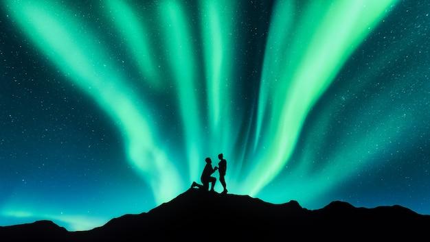 Aurora boreal e silhuetas de um homem fazendo pedido de casamento para sua namorada na colina. paisagem com céu estrelado, aurora boreal Foto Premium