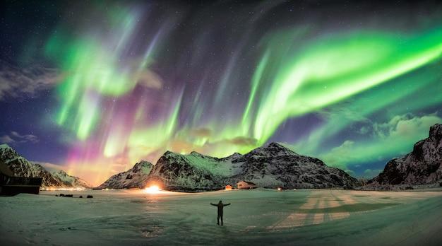 Aurora boreal (luzes do norte) sobre a montanha com uma pessoa Foto Premium