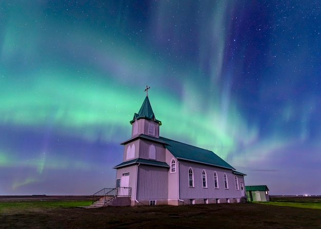 Aurora boreal sobre a histórica igreja luterana da paz em saskatchewan, canadá Foto Premium