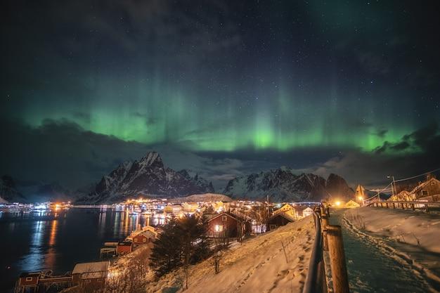 Aurora boreal sobre a luz da aldeia escandinava brilhando no inverno Foto Premium