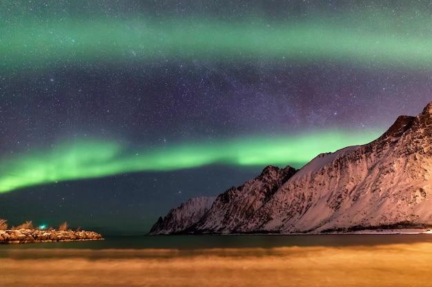 Aurora boreal sobre a praia de ersfjord. maré baixa. ilha de senja à noite, na noruega. europa Foto Premium