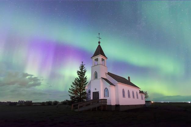 Aurora boreal sobre uma igreja histórica nas pradarias de saskatchewan, canadá Foto Premium