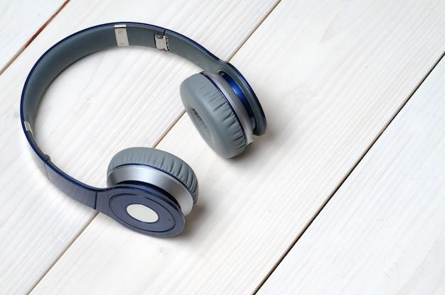 Auscultadores modernos em azul e prateado para ouvir música em madeira branca Foto Premium