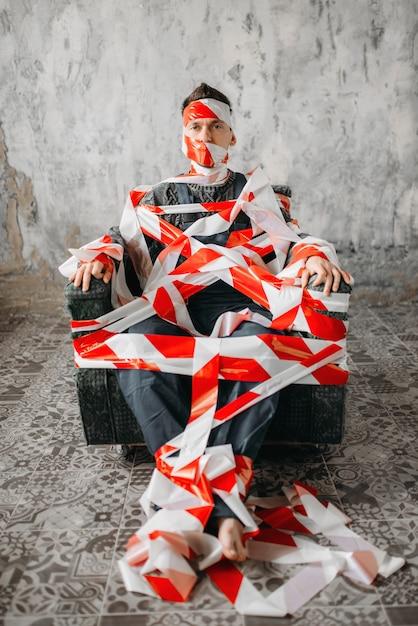 Autista sentado em uma cadeira no meio da sala Foto Premium