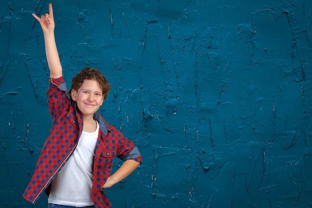 Auto confiante menino com punhos levantados, celebrando um sucesso recente Foto Premium