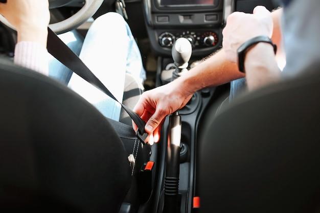 Auto instrutor masculino faz exame em jovem. cara segura o cinto da garota na mão e quer trancá-lo. cortar vista. sentado no carro. examinando a jovem mulher. Foto Premium