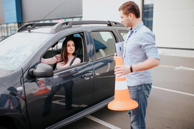 Auto instrutor masculino faz exame em jovem. ficar fora do carro com sinal laranja nas mãos. olhe mulher no carro. studenthold feminino mãos no volante e olhar para o instrutor. Foto Premium