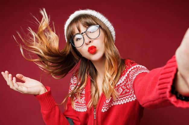 Auto-retrato de mulher de cabelos compridos feliz em roupas de inverno Foto gratuita
