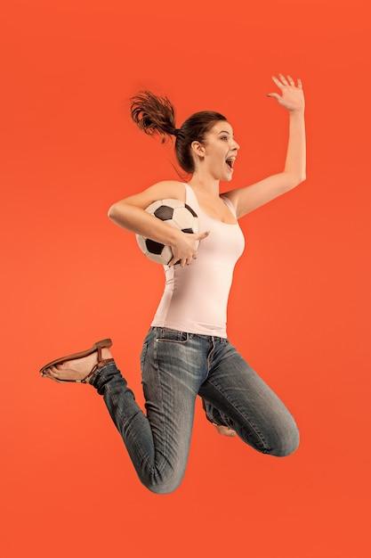 Avance para a vitória. jovem mulher como jogadora de futebol americano pulando e chutando uma bola no vermelho Foto gratuita