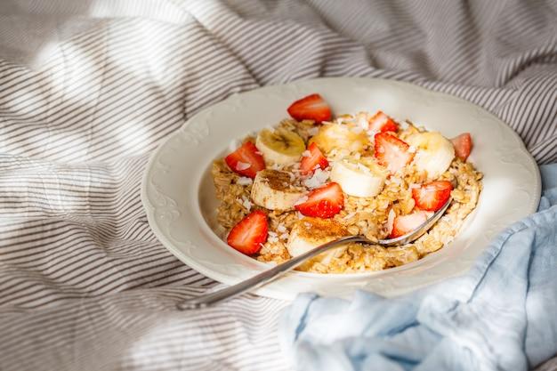 Aveia com banana, morangos e manteiga de amendoim em chapa branca na cama backgrond. Foto Premium