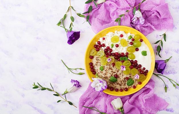 Aveia deliciosa e saudável com uvas, iogurte e queijo cottage. café da manhã saudável. comida de fitness. nutrição apropriada. postura plana. vista do topo. Foto gratuita