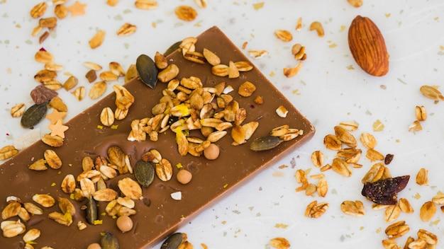 Aveia e frutas secas na barra de chocolate contra o pano de fundo branco Foto gratuita