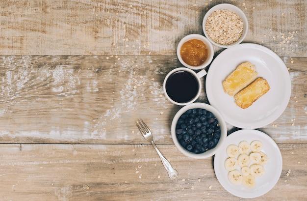 Aveia; geléia; café; amoras; fatia de banana e torradas na prancha de madeira Foto gratuita