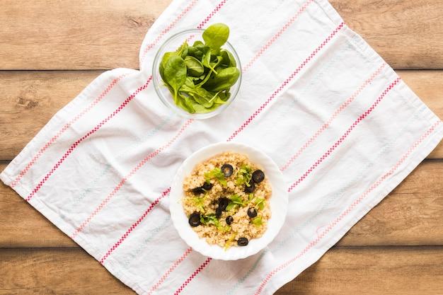 Aveia saudável, guarnecida com folhas de manjericão e azeite no café da manhã na mesa de madeira Foto gratuita