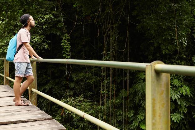 Aventura e turismo. estudante caucasiano bonito, caminhadas na floresta tropical. jovem alpinista com mochila em pé na ponte de madeira e olhando para a floresta verde Foto gratuita