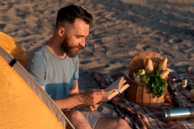 Aventureiro lateral sentado e lendo Foto gratuita