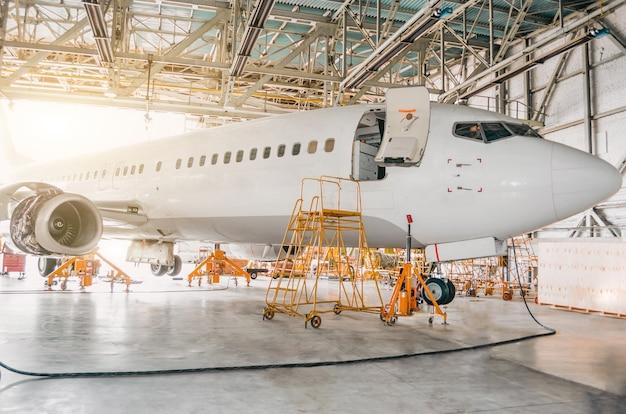 Avião comercial em hangar com portão aberto para o serviço. Foto Premium