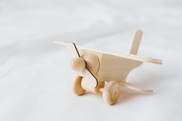 Avião de brinquedo de madeira fica em um fundo branco Foto Premium