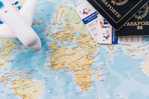 Avião de brinquedo; passaportes e franquias de bagagem no mapa Foto gratuita