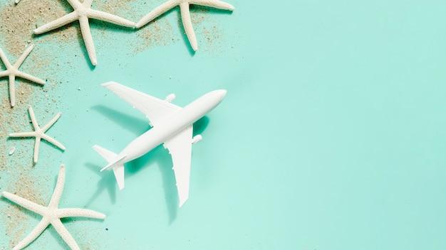 Avião de brinquedo pequeno com estrelas do mar na mesa Foto gratuita