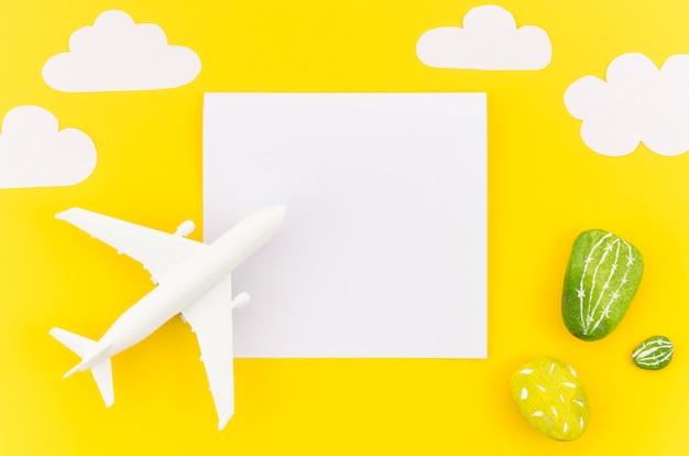 Avião de brinquedo pequeno com nuvens e papel Foto gratuita