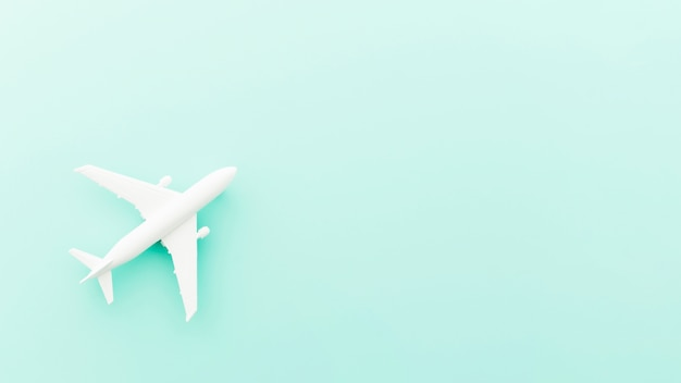 Avião de brinquedo pequeno na mesa azul Foto gratuita