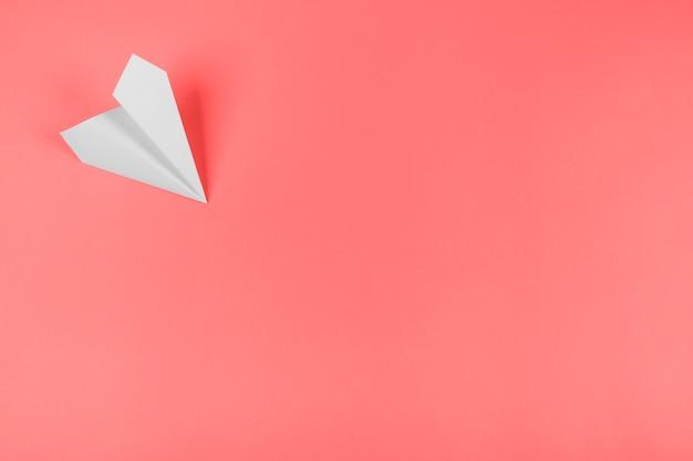 Avião de papel branco no canto do fundo coral Foto gratuita