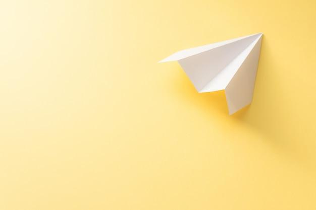 Avião de papel branco sobre fundo amarelo. conceito de viagens coloridas Foto Premium