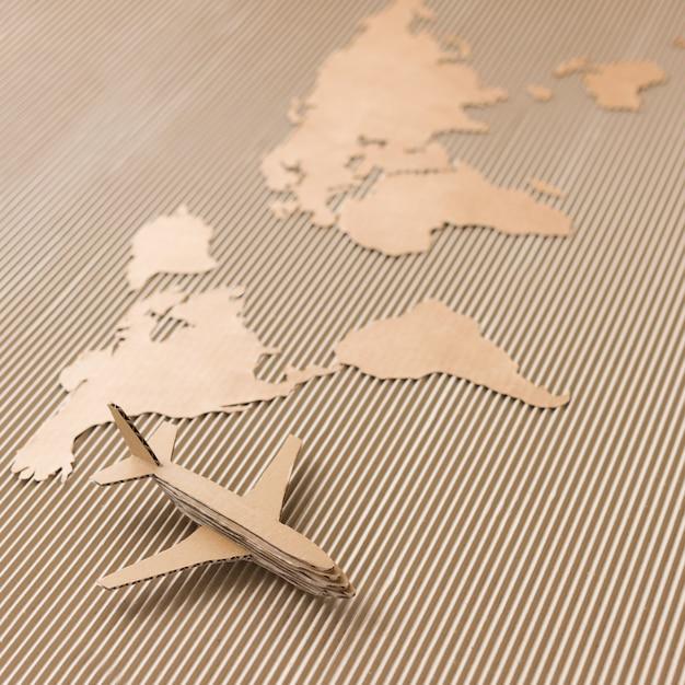 Avião em um mapa do mundo feito de papelão ondulado Foto Premium