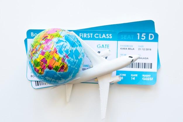 Avião pequeno com bilhetes e globo Foto Premium