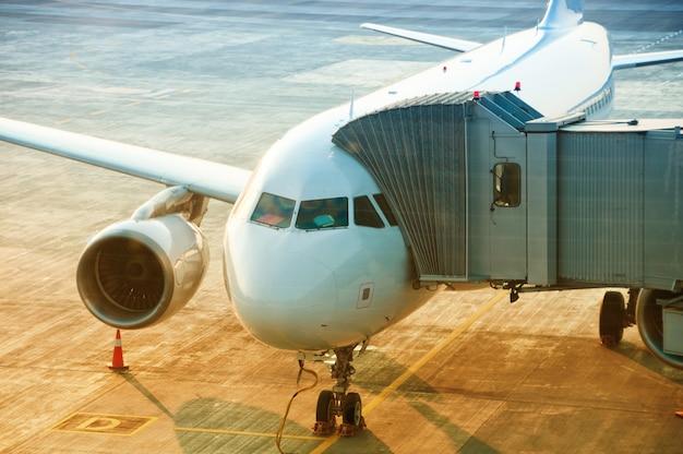 Avião se preparando para decolar no aeroporto, ponte de embarque de passageiros anexada à aeronave Foto Premium