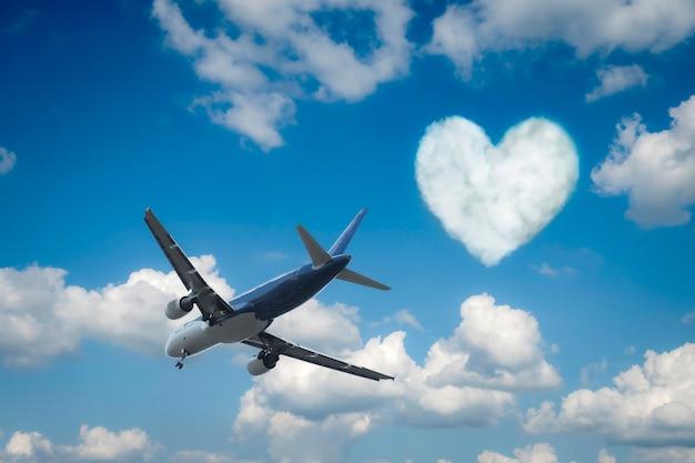 Avião sobre as nuvens e um coração Foto Premium