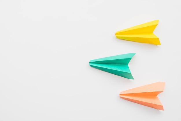 Aviões de papel voando em formação de cunha Foto gratuita
