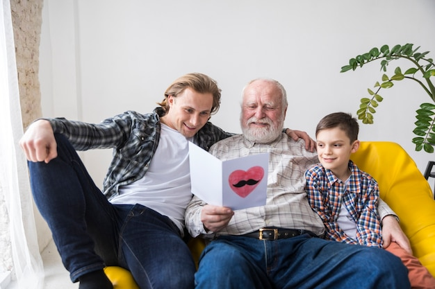 Avô alegre que lê o cartão handmade do aniversário Foto gratuita