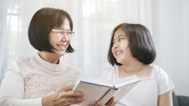 Avó asiática feliz e linda menina lendo livro juntos em casa Foto Premium