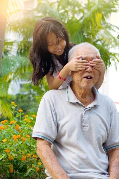 Avô asiático brincando com seus netos no parque Foto Premium