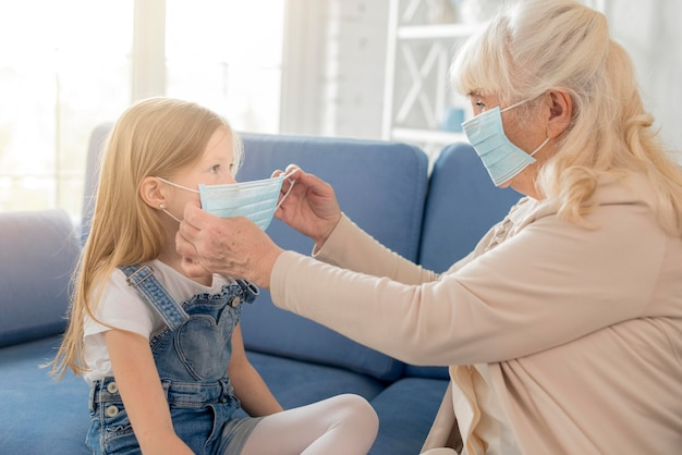 Avó colocando máscara para menina Foto gratuita