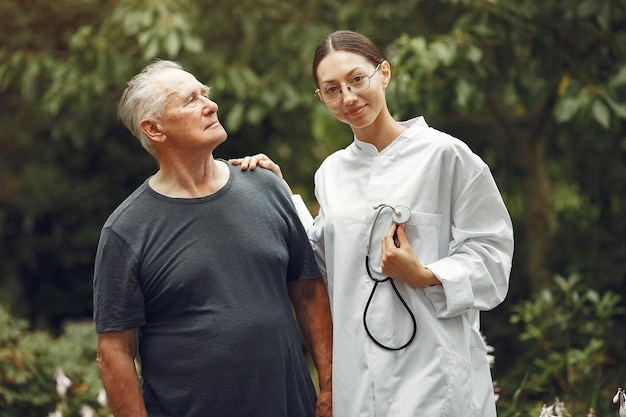 Avô com cadeira de rodas auxiliado por enfermeira ao ar livre. último homem e jovem cuidador no parque. Foto gratuita