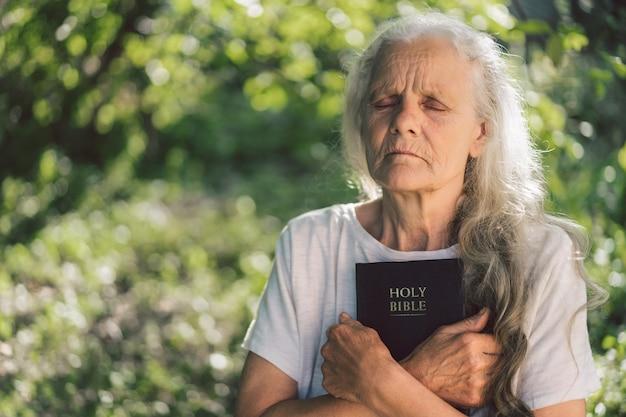 Avó de cabelos grisalhos tem a bíblia nas mãos. Foto Premium