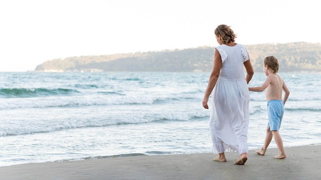 Avó e criança caminhando na praia Foto gratuita