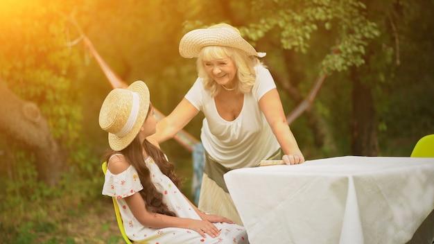 Avó e neta estão à mesa no jardim Foto Premium
